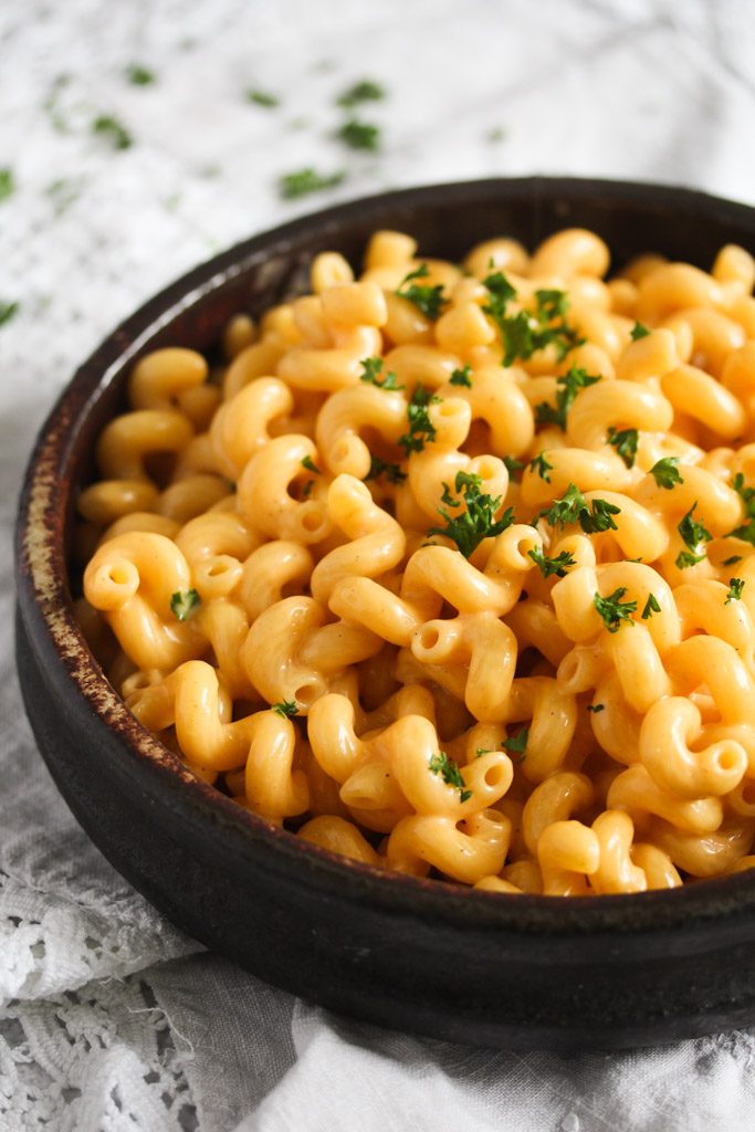brown bowl with cheese pasta sprinkled with parsley on a white vintage cloth.