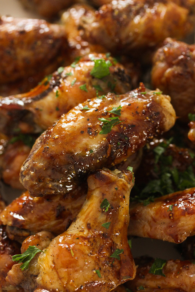 close up of many sticky baked chicken wings.