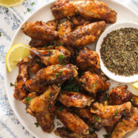close up of many wings on a plate with a bowl of spices.